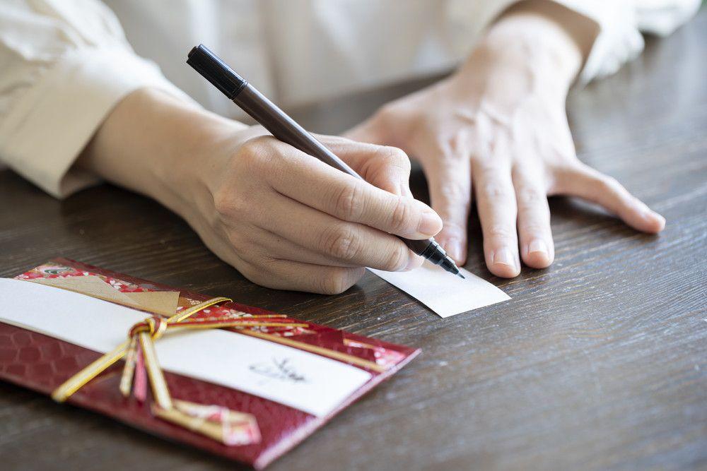 ご祝儀袋に筆ペンで名前を書いている