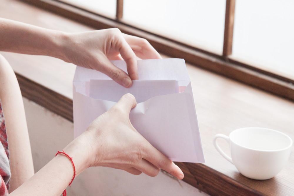 招待状の封を開けて中身をチェックしようとしている女性