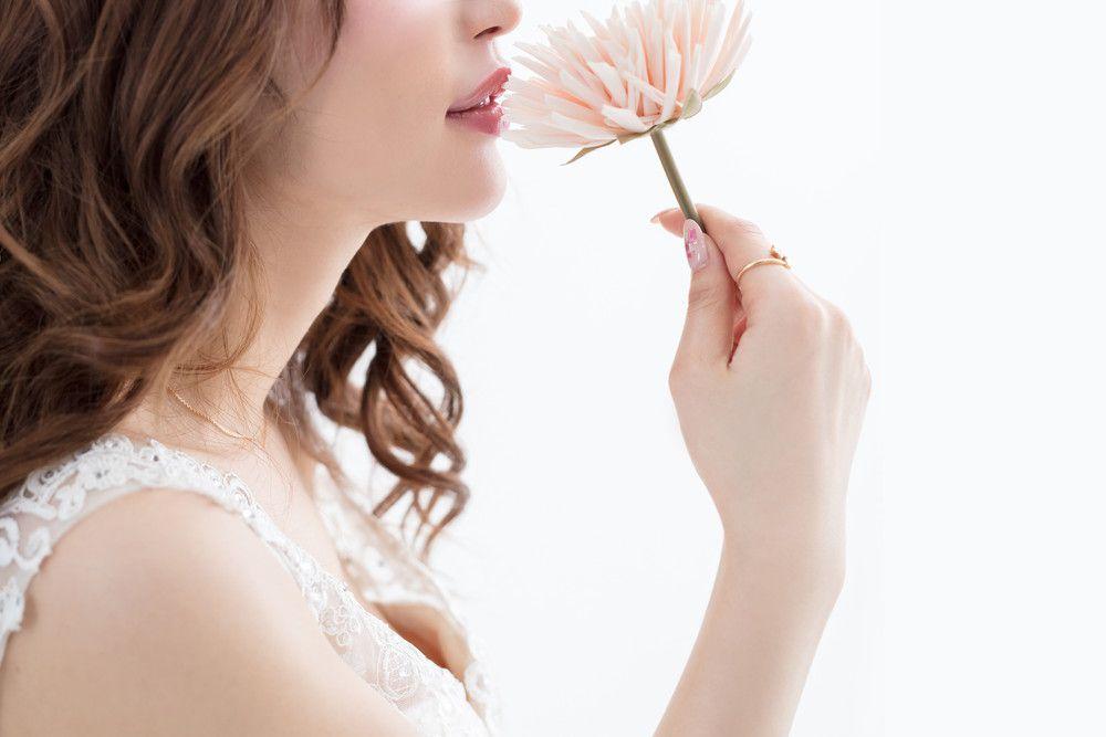 淡いピンクの花を持っている女性の口元