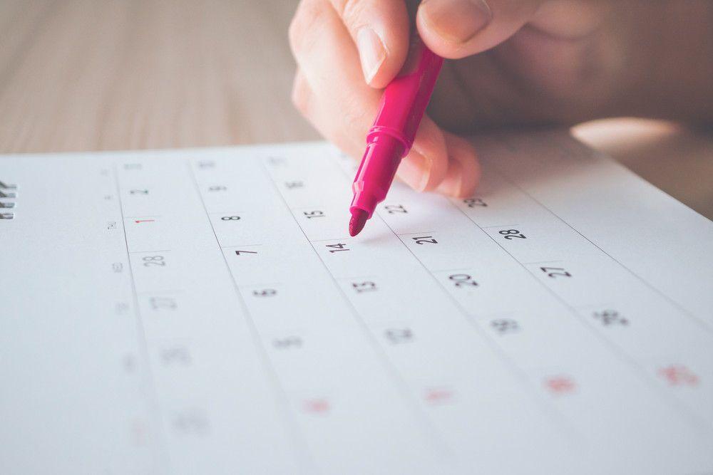 カレンダーの結婚式開催日にペンでしるしをつけようとしている