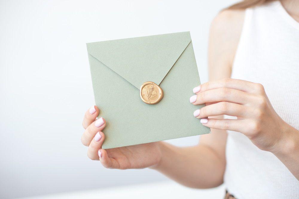 モスグリーンの封筒にゴールドの封蝋がおしゃれな招待状を持っている女性