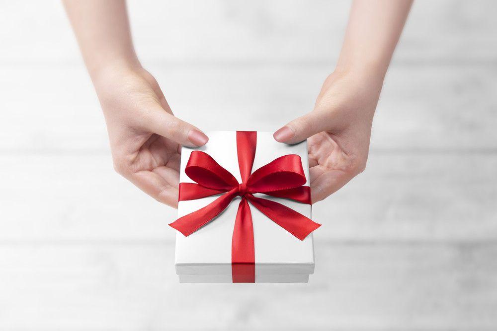 赤いリボンのプレゼントを渡している手元
