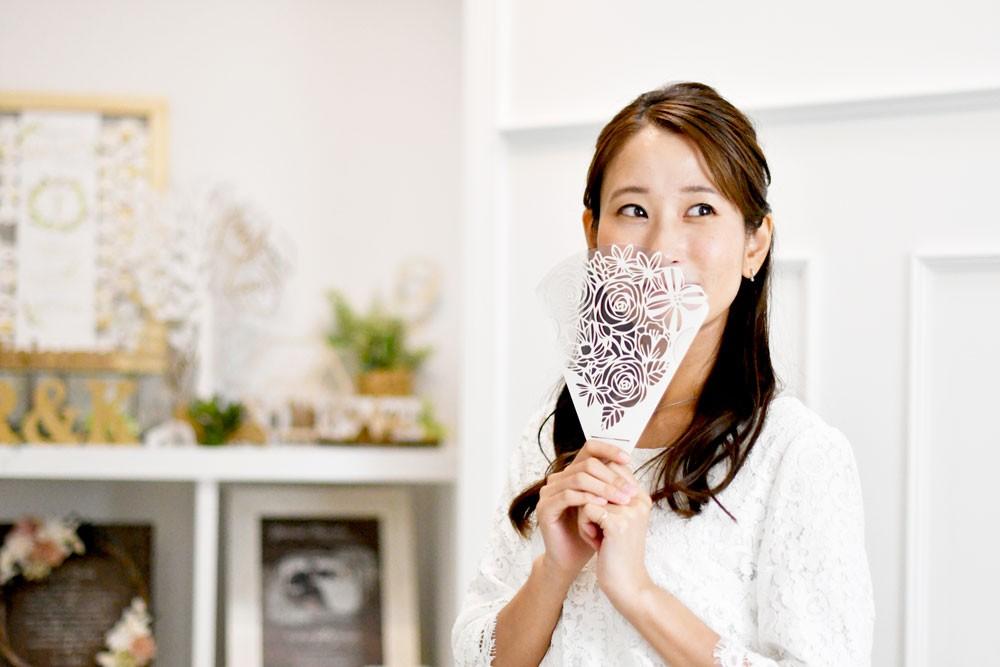 花束のような形にレーザー加工されたフェイスシールドを口元に添えている女性