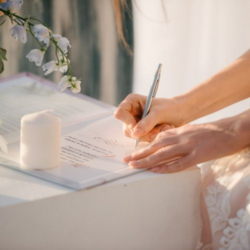 the bride in a wedding dress signs in the contract close up