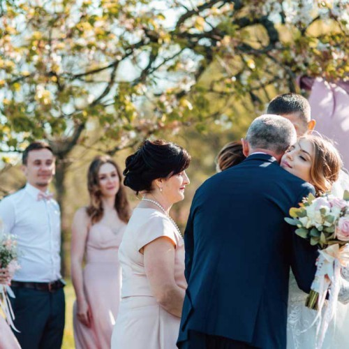 Bride and groom after wedding ceremony. Parents welcome newlyweds to marry. Stylish happy smiling newlyweds on the outdoor
