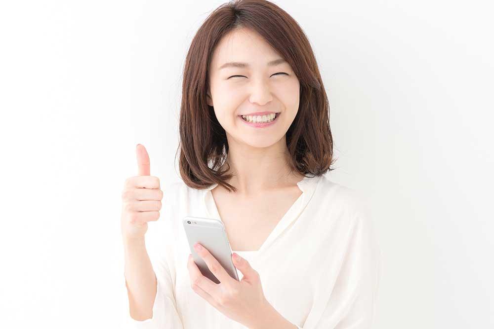 スマホを手に親指を立てる笑顔の女性