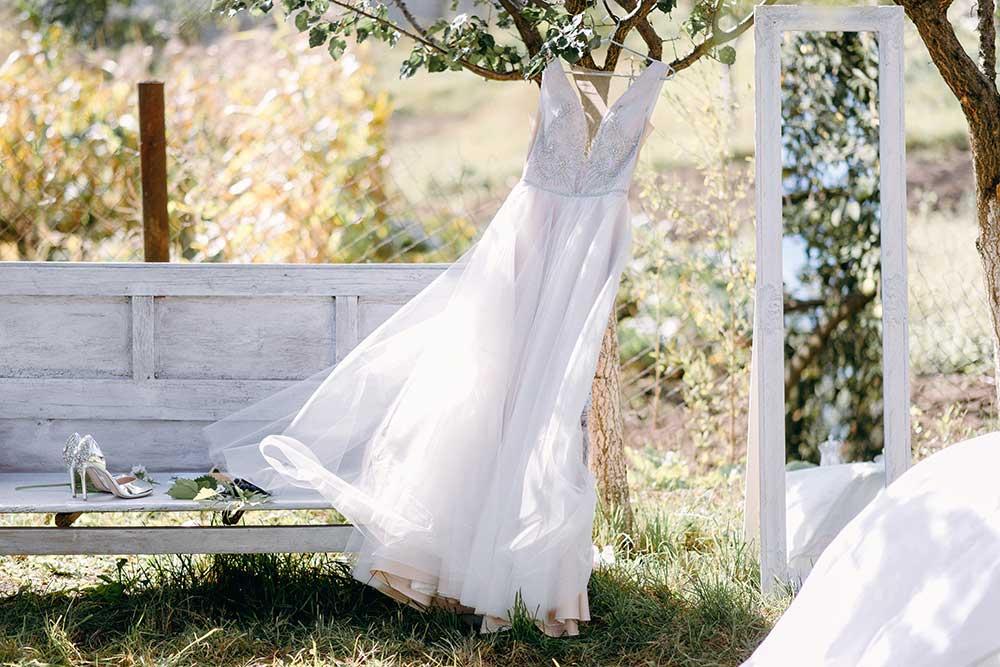 203347630屋外の木にハンガーにつるしたウェディングドレスが風になびく風景