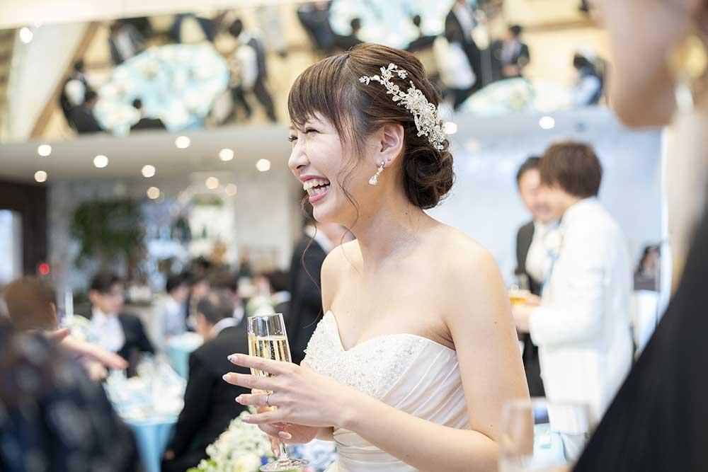 256958314グラスを手にゲストと楽しそうに歓談する花嫁