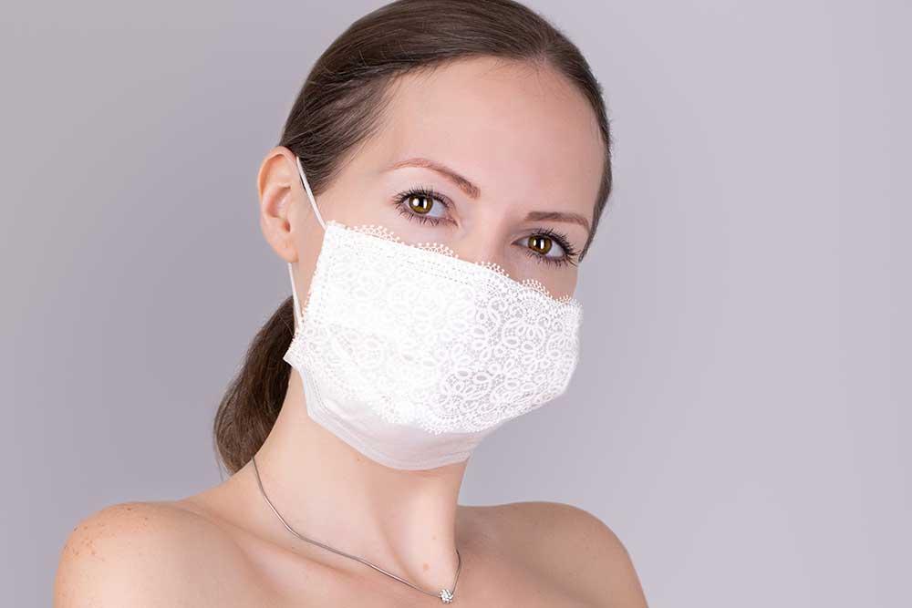 白いレースの飾り付きマスクを着用している女性