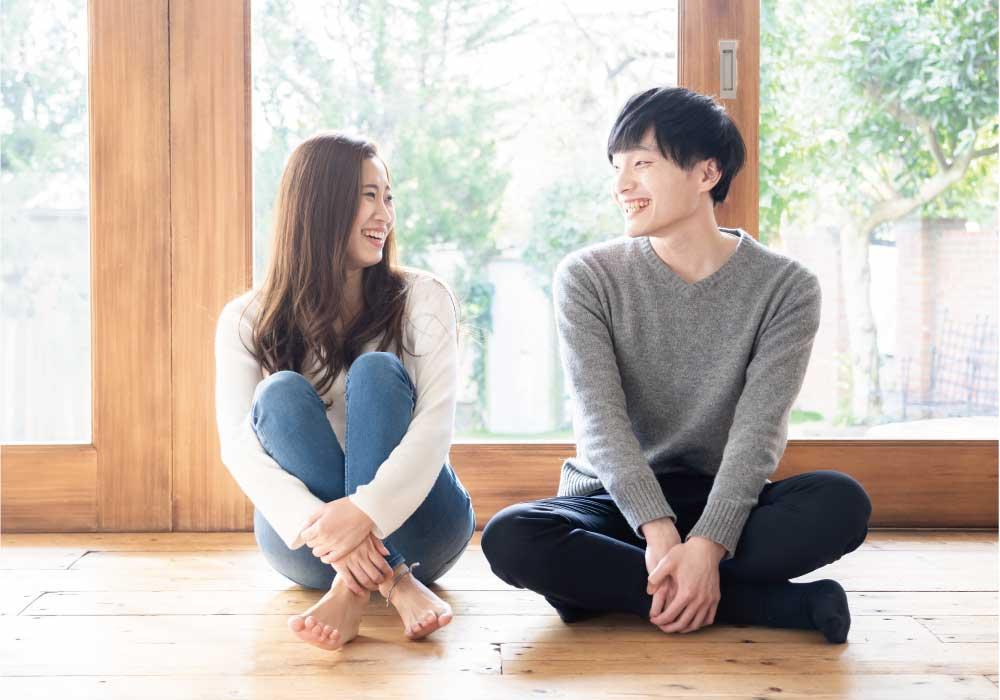床に座って見つめ合うカップル