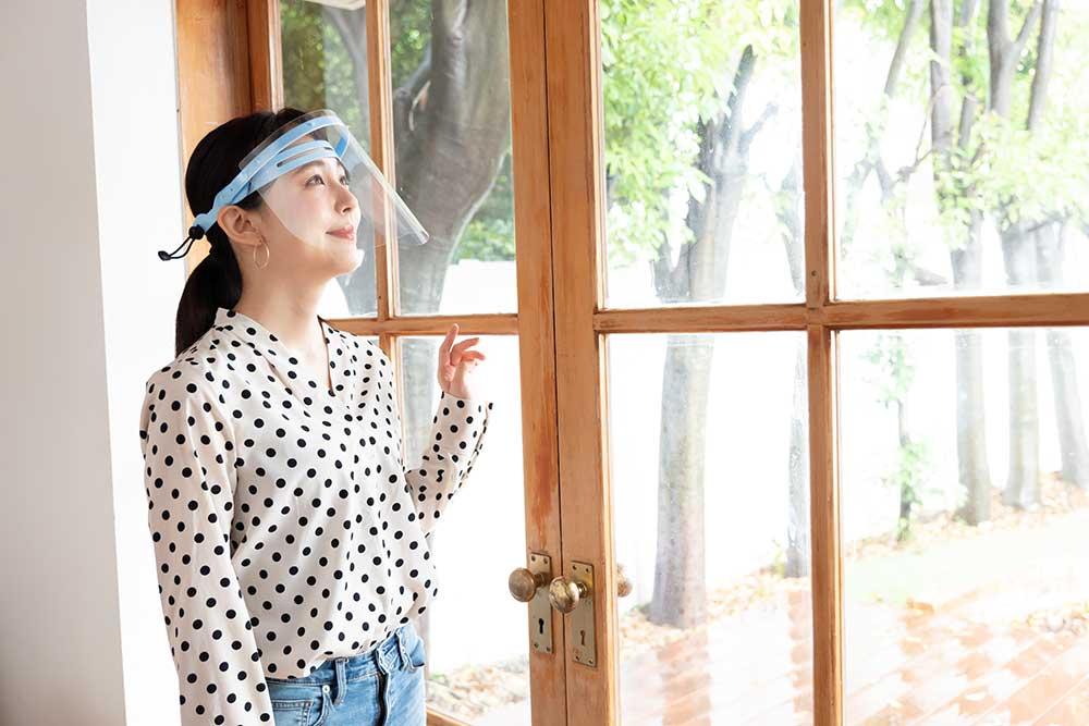 フェイスシールドをした女性が窓の外を眺めている