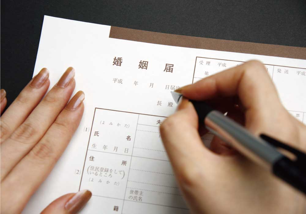 入籍するため婚姻届を書いている女性の手元