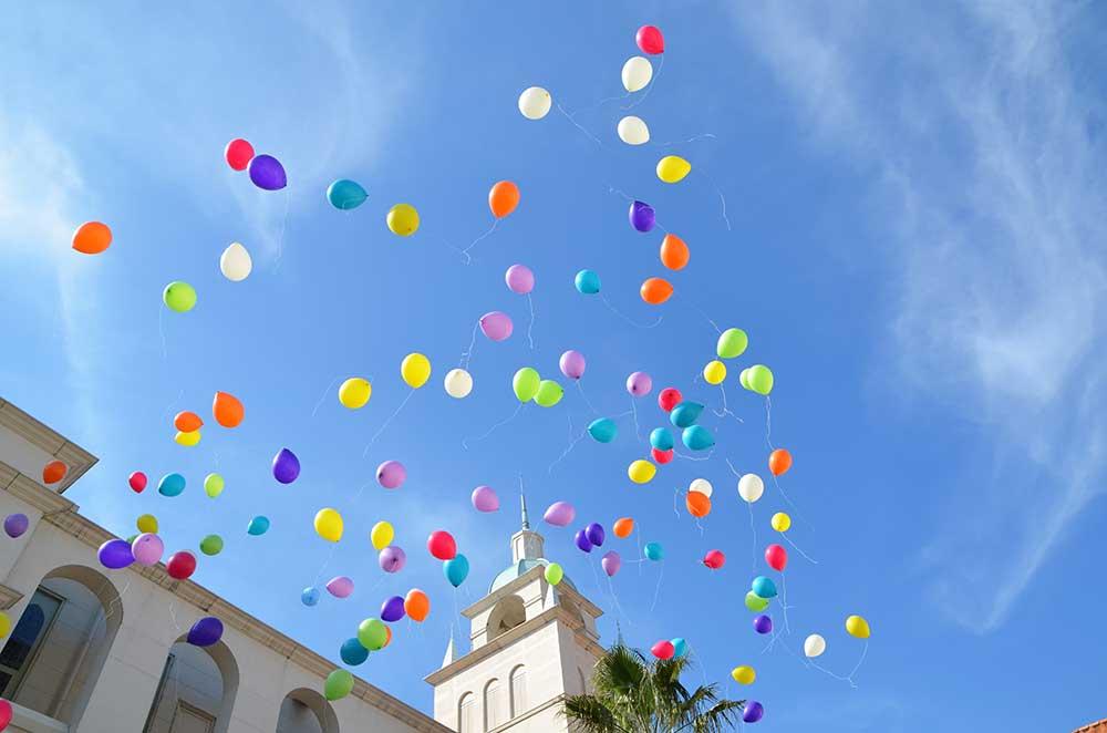 カラフルな風船が青空に放たれているバルーンリリースの様子