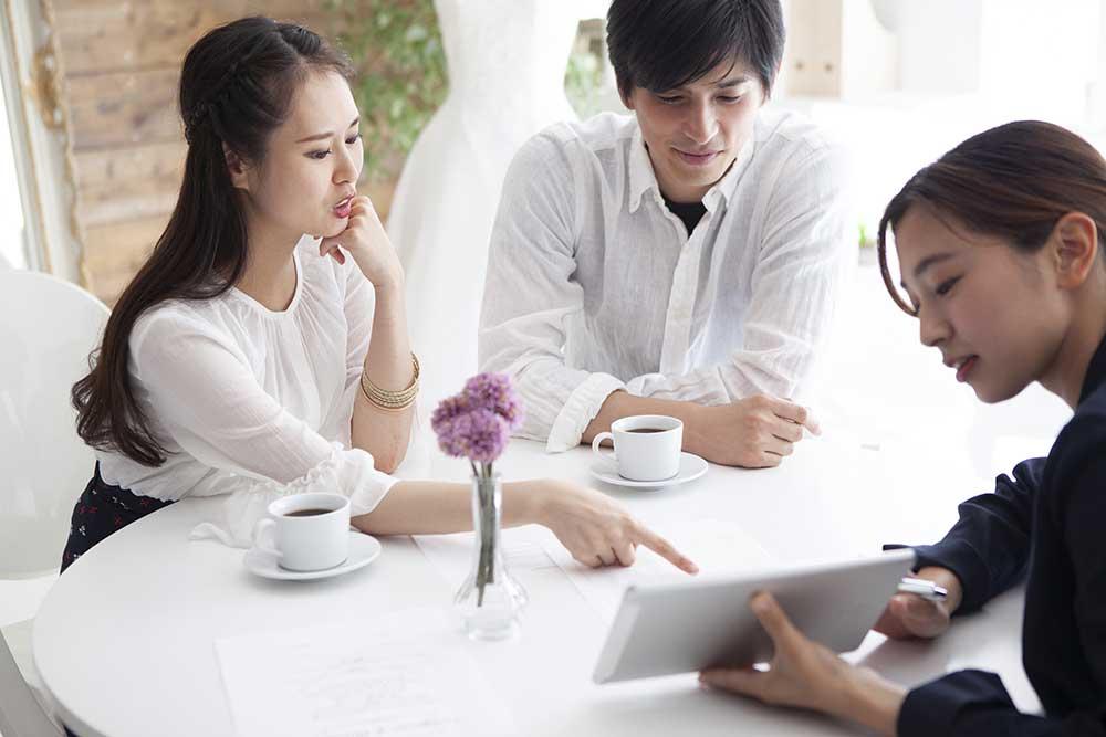 ウェディングプランナーとタブレットを見ながら相談するカップル