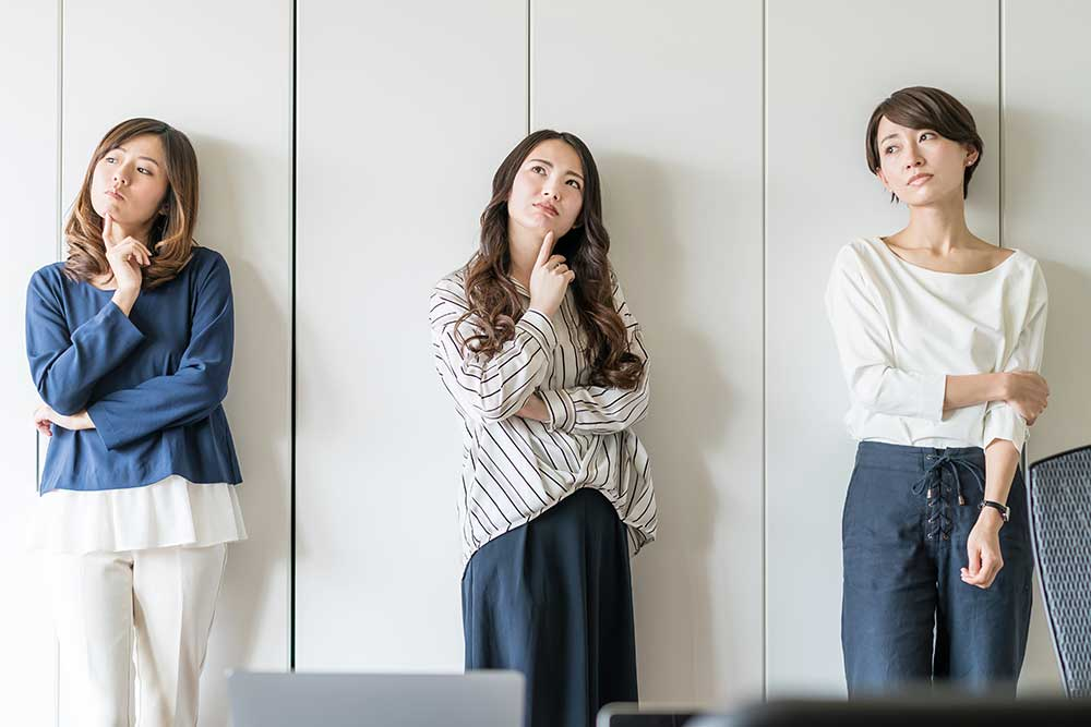 考え事をしながら上を見ている女性3人