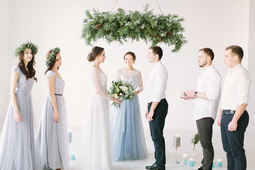 Bride and groom during wedding ceremony indoors. Ceremony master performing speech. Bridesmaids and groommen are smiling and happy