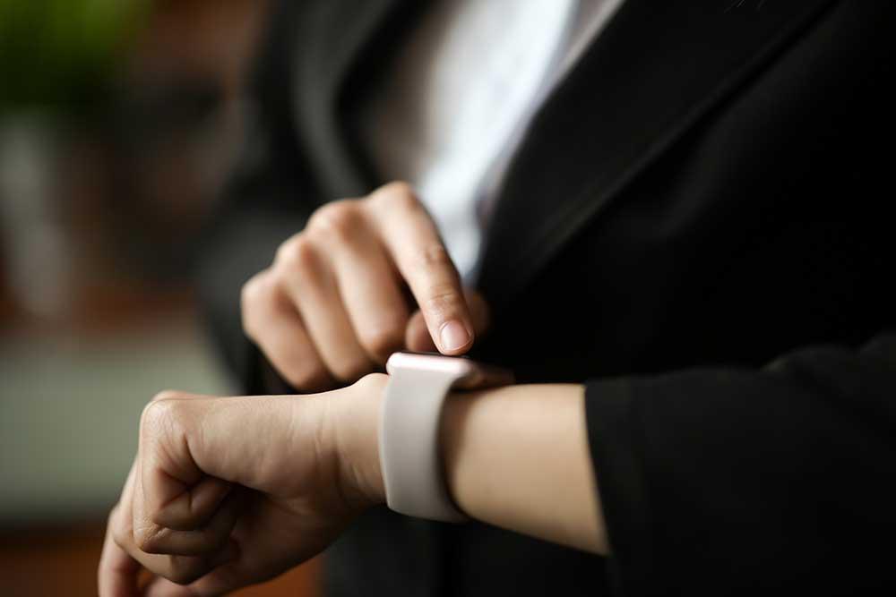 時計を確認するスーツ姿の女性
