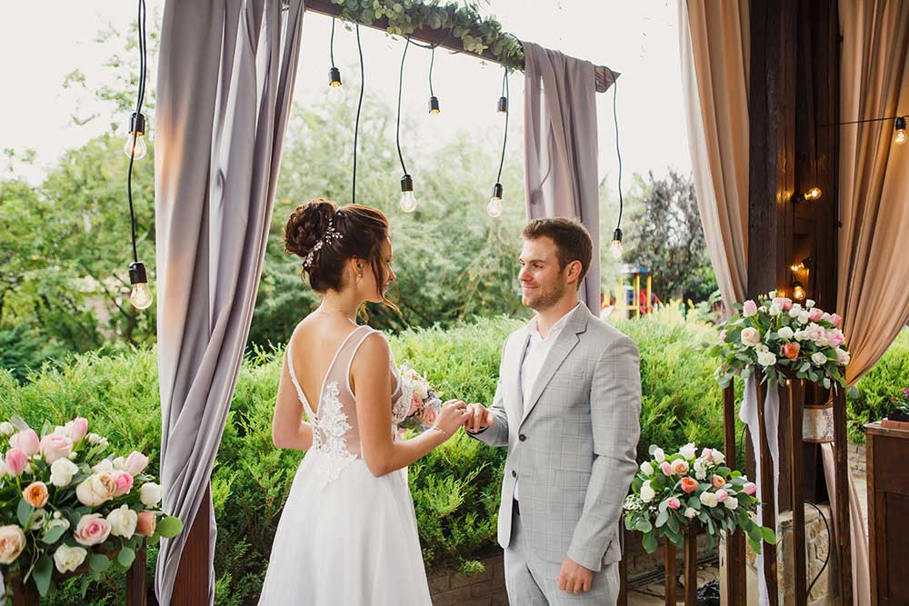 Beautiful wedding couple. The bride and groom are standing at the wedding ceremony. The bride in a beautiful dress тhe groom is dressed stylishly