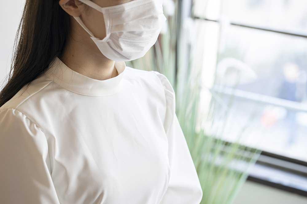 マスクをつけた白い服を着た女性上半身