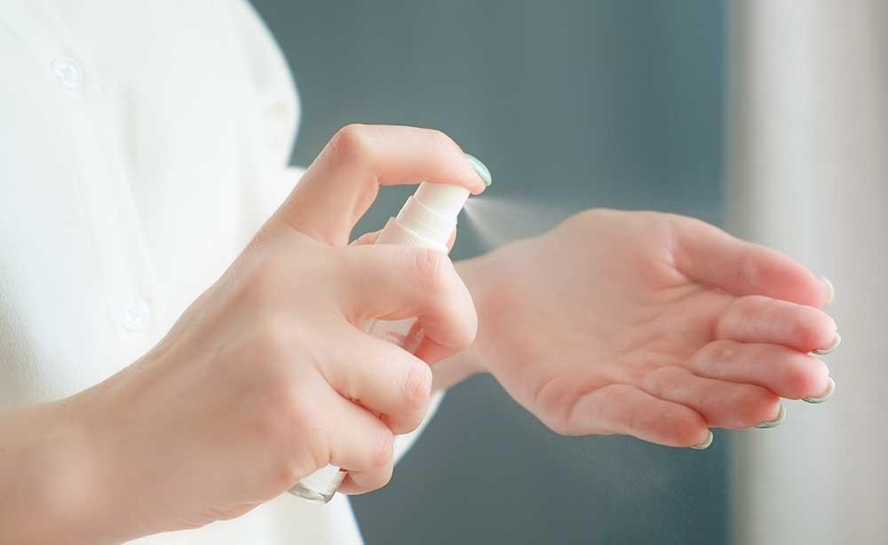手指にアルコール消毒スプレーを吹きかけている女性の手元