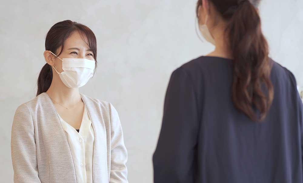お互いマスクをして笑顔で話しをする女性二人