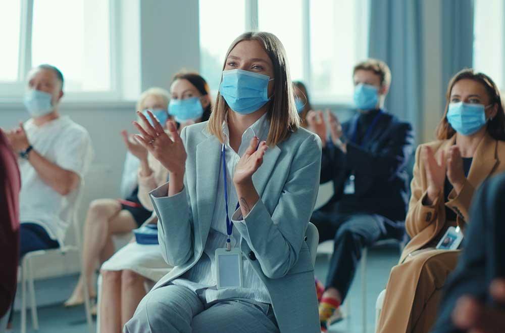 椅子に座ったマスクを着用した男女が拍手をしている