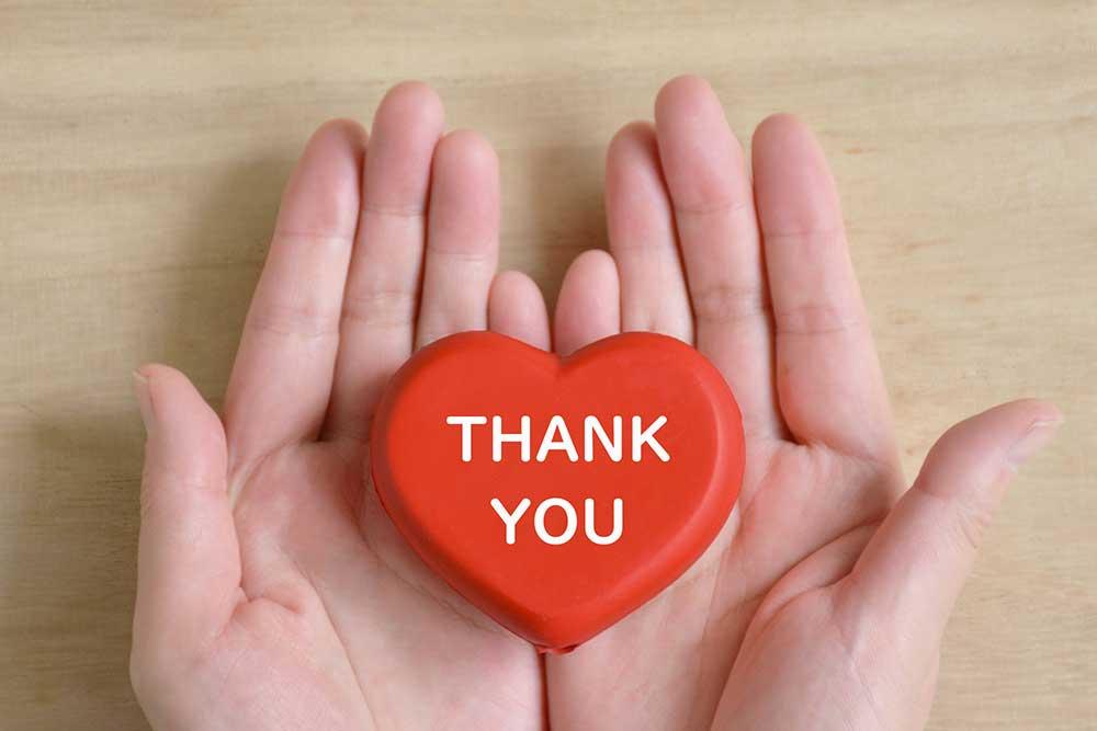 Thankyouと書かれた赤いハートを手に持つ