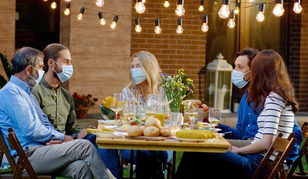 屋外でマスクをしたまま食事を楽しむ男女