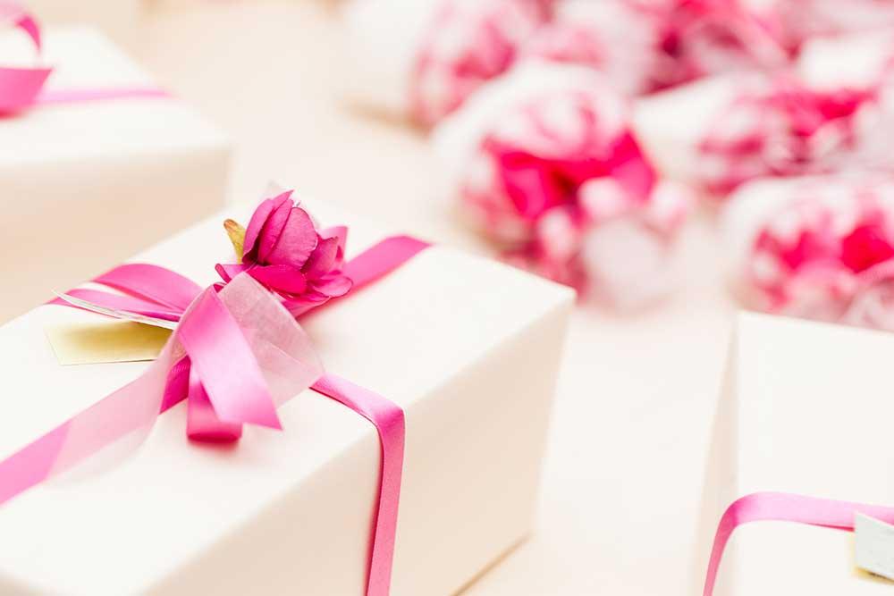 ピンクのリボンとお花を飾り付けた白いプレゼントボックスがたくさん並んでいる
