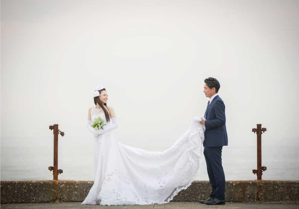 新婦の白いウェディングドレスの裾を持つ新郎