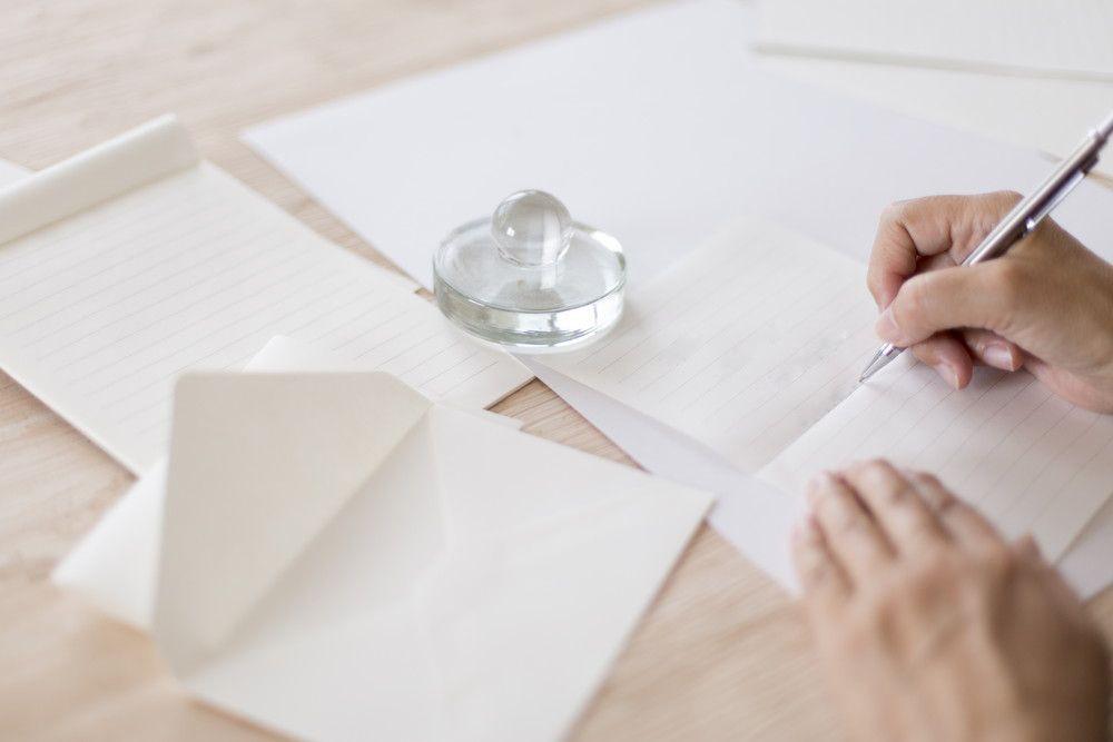 白い封筒&便せんに手紙を書く女性の手元