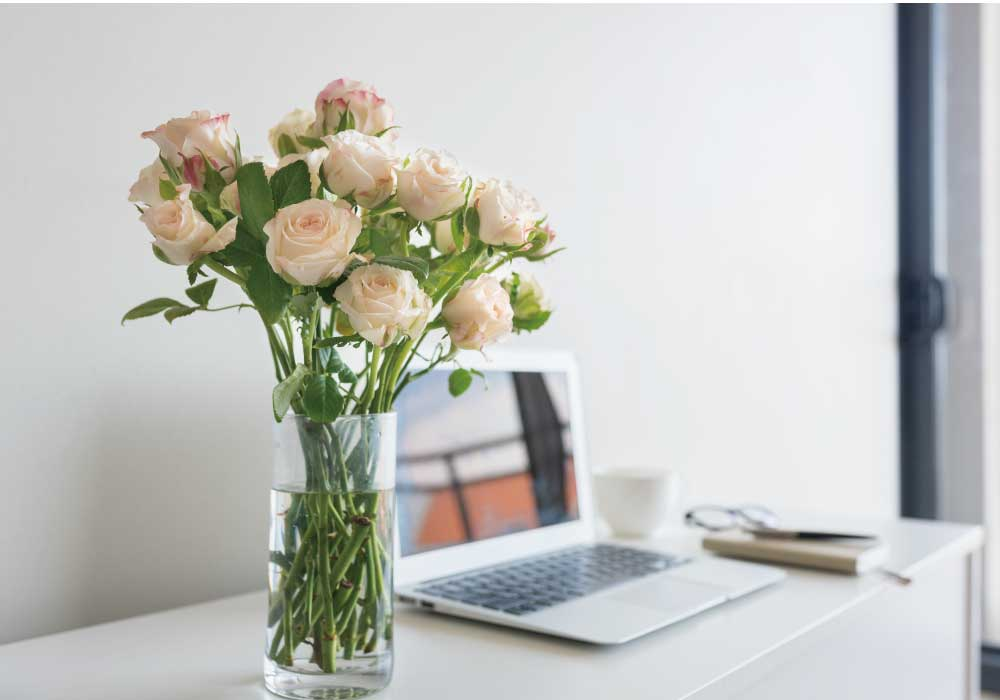 パソコンの横に置かれた花瓶に生けられた薄いピンクのバラの花束