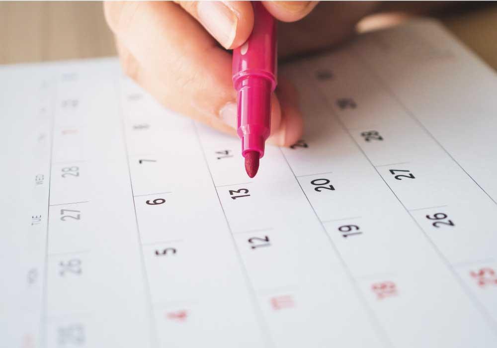 カレンダーに赤いペンで丸付けする画像