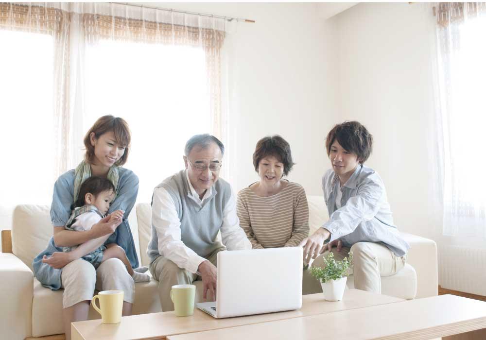 パソコンを見ながら談笑するシニア夫婦と息子夫婦と孫