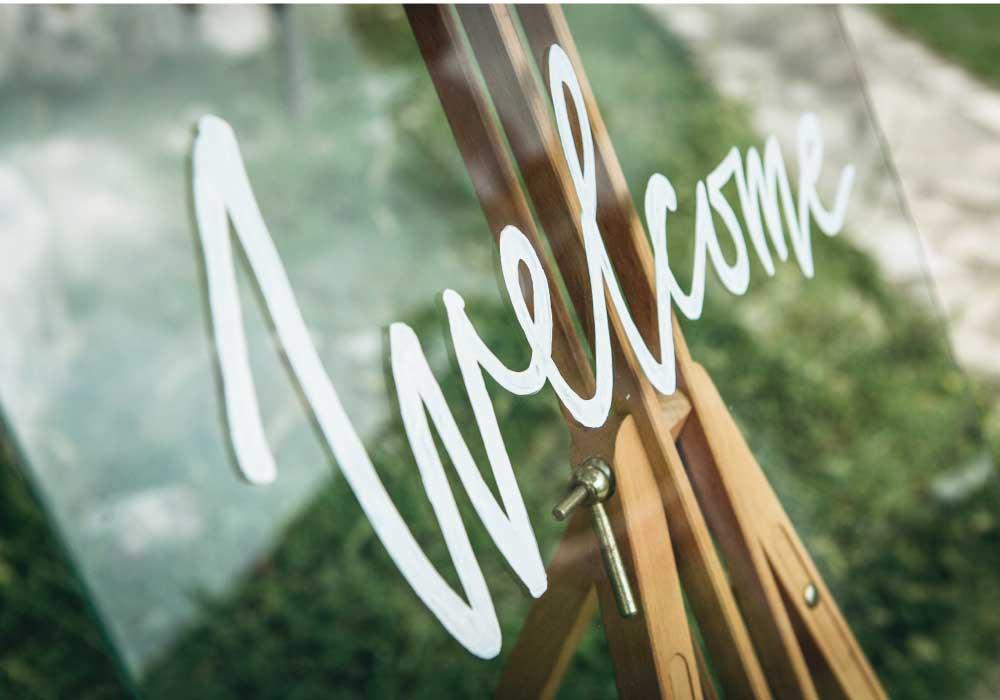 透明のアクリルに白い文字でウェルカムと書かれたウェルカムボード
