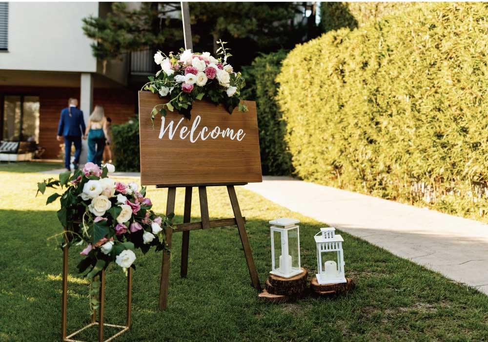 ピンクのお花が飾りつけてある木製のウェルカムボードとランタンの飾りつけ