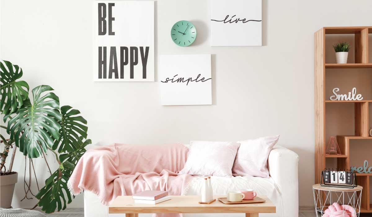 薄いピンクと白を基調にしたポスターと緑の時計が飾ってある部屋