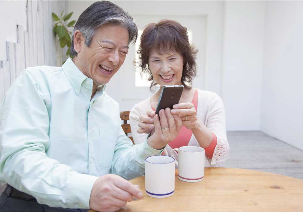 スマホでオンライン通話をしながら笑っているシニア夫婦