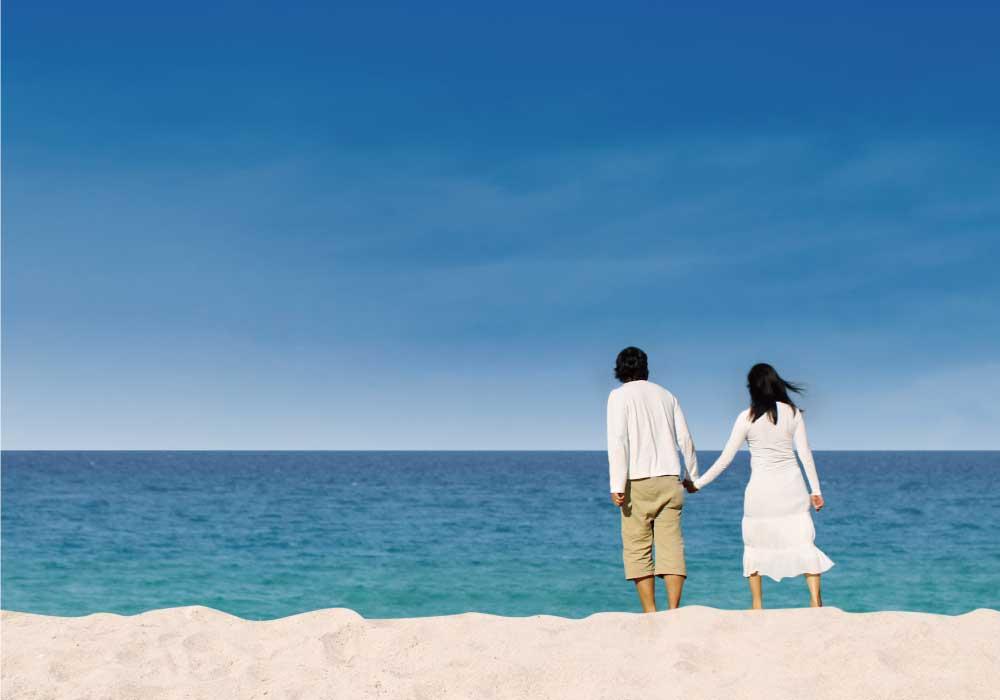 青空の下で海辺で手をつないで海を眺める若いカップル