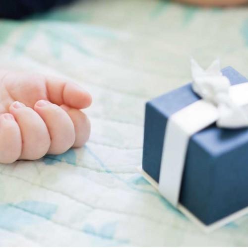 寝ている赤ちゃんの手と横に置いてあるギフトボックス