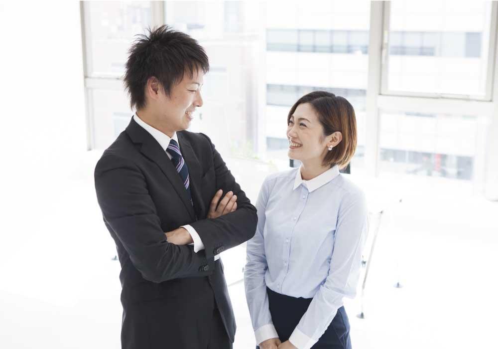 笑顔で会話するスーツを着た若い日本人男性と女性