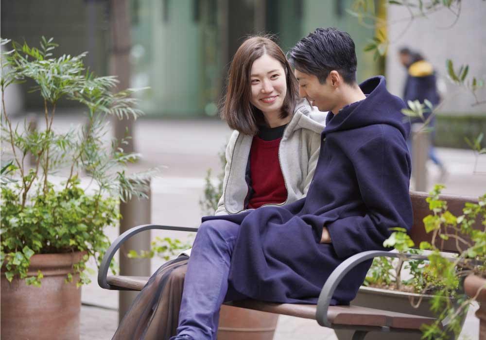 ベンチに座って談笑する若いカップル