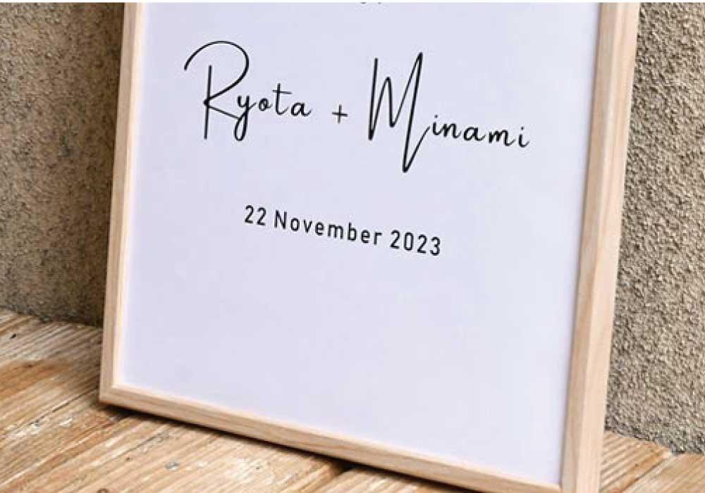 白地に黒字で新郎新婦名と日付が入った木製フレームのウェルカムボード