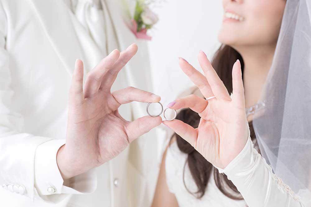 結婚指輪を手に持つ新郎新婦