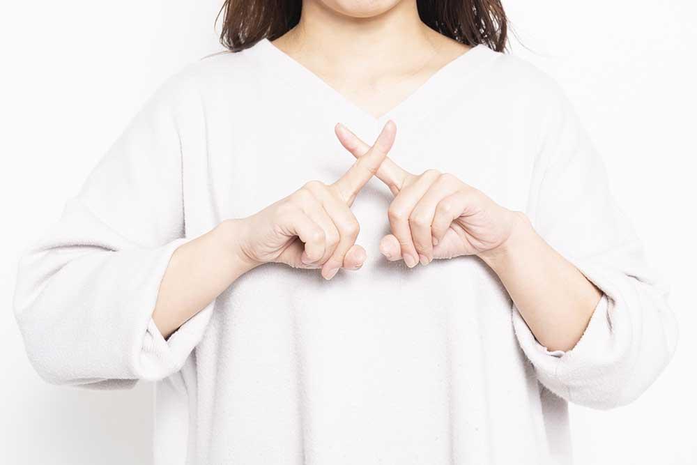 胸の前で指でNGマークを作る女性