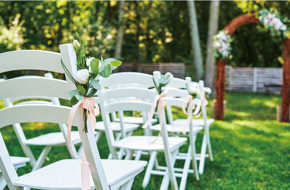 ガーデンウェディング用に並べられたお花のブーケが付いた白い椅子