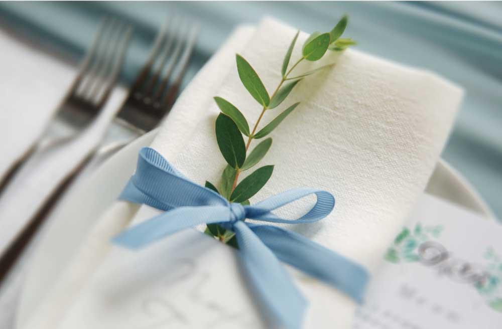 水色のリボンでナプキンに結ばれた葉っぱの結婚式テーブルのコーディネート
