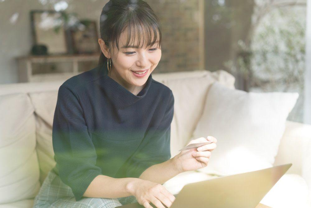 パソコンでクレジットカード片手に通販をしている女性