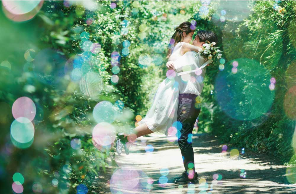 緑の木漏れ日の中で抱き合う若いカップル