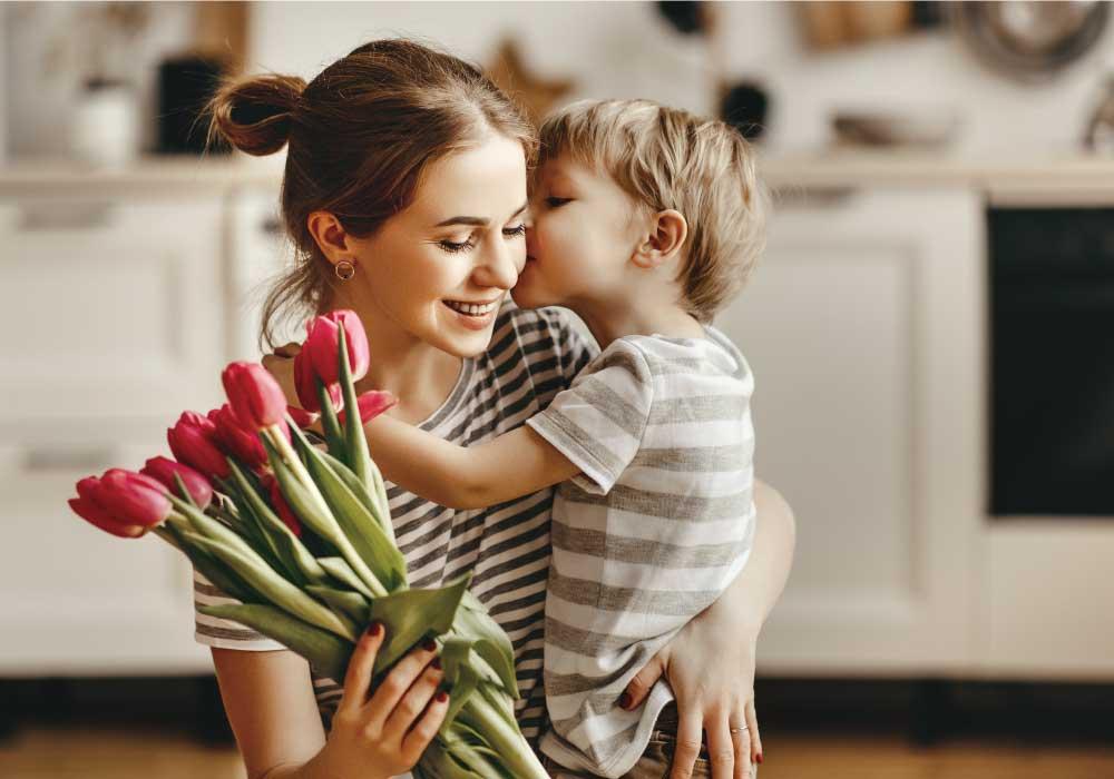 チューリップの花束を持った笑顔の母親に抱き着いてキスをする小さい男の子